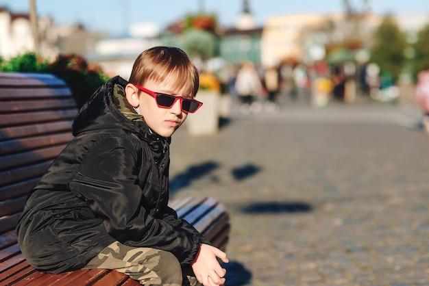 Garoto pré-adolescente bonito vestindo jaqueta preta, óculos de sol da moda e roupas elegantes de inverno