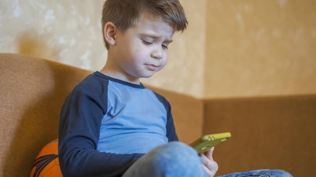 Garoto pré-escolar chateado por perder em um jogo para celular.