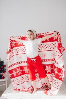 Garoto pulando na cama coberta com um cobertor