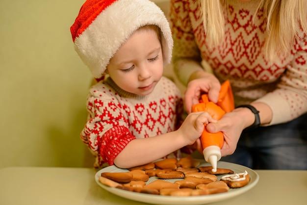 Garoto risonho assar biscoitos de gengibre festivos caseiros. criança engraçada preparar comida de férias para o papai noel.