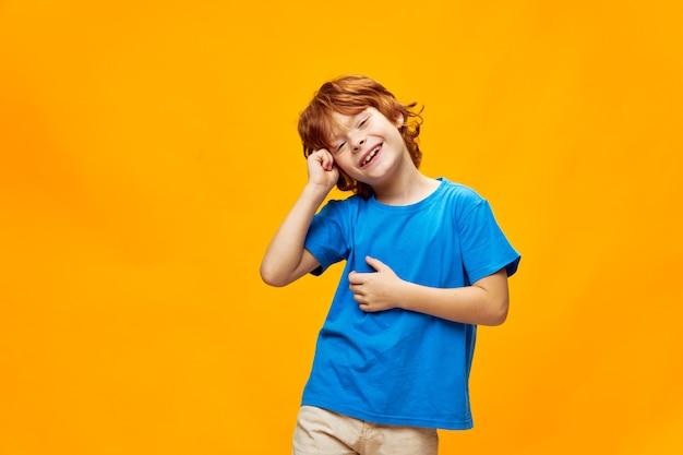 Garoto ruivo alegre inclinou a cabeça para o lado com a mão perto do rosto, sorrindo, camiseta azul vista cortada