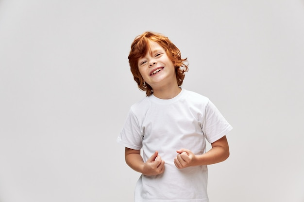 Garoto ruivo alegre segurando as mãos na frente dele sorriso de camiseta branca