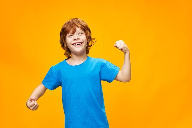 Garoto ruivo fazendo gestos com as mãos e camiseta azul