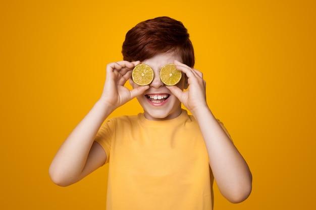 Garoto ruivo feliz cobrindo os olhos com limões e sorrindo em uma parede amarela