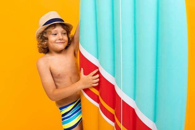 Garoto ruivo feliz com um chapéu de verão, um colchão de ar sobre fundo amarelo
