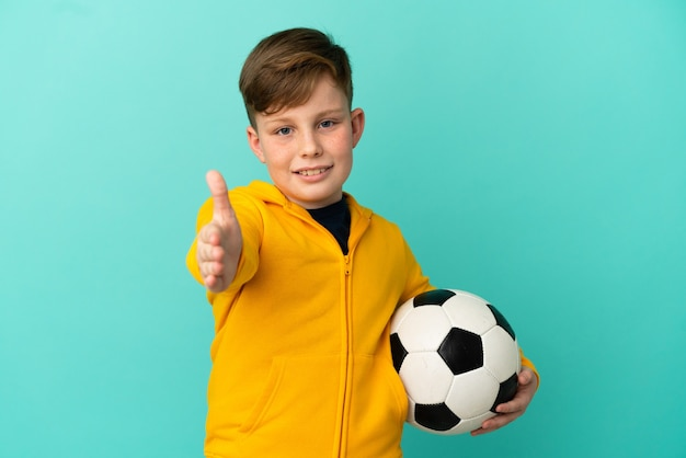 Garoto ruivo jogando futebol isolado em um fundo azul apertando as mãos para fechar um bom negócio