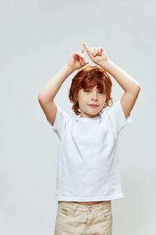 Garoto ruivo segurando as mãos acima da cabeça mostrando camiseta branca para cima