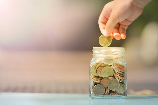 Garoto salvando moeda no cofrinho de vidro