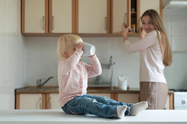 Garoto se senta à mesa da cozinha e bebe da xícara contra o fundo surpreso da mãe.