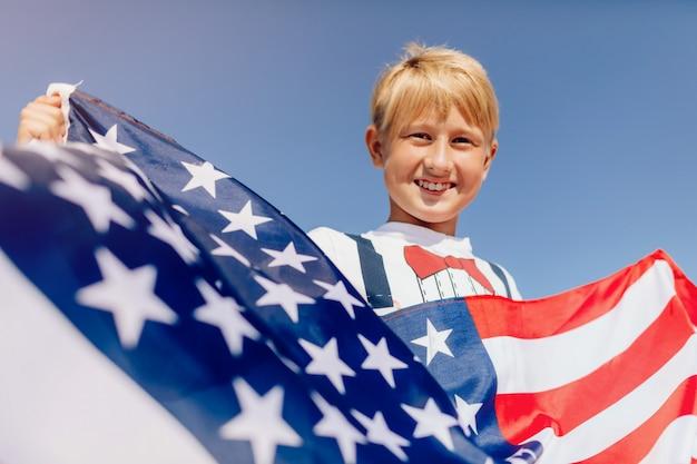 Garoto segurando a bandeira americana. patriotas da américa.