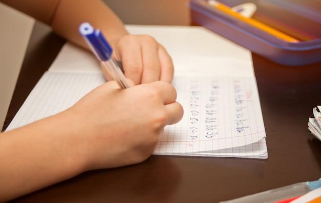 Garoto segurando a caneta e escrevendo no caderno