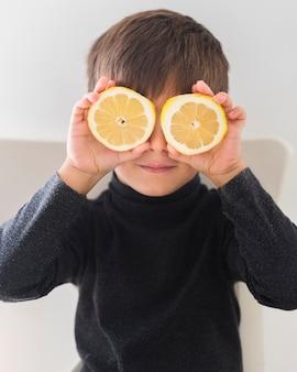 Garoto segurando as metades da laranja sobre os olhos