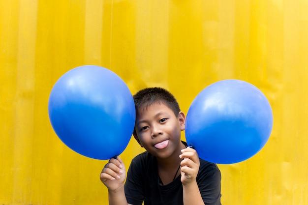 Garoto segurando balões azuis com a língua para fora brincando com veio