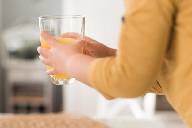 Garoto segurando copo de suco de laranja