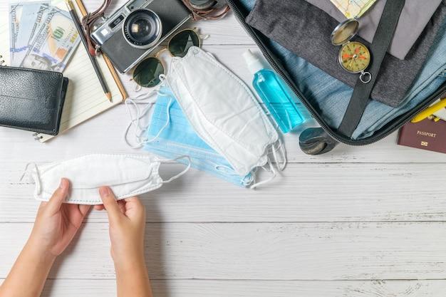 Garoto segurando máscara e mala, câmera vintage, caderno, mapa em madeira branca e espaço de cópia. viajar e prevenir o covid 19 conceito