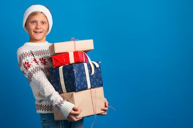 Garoto segurando presentes de natal