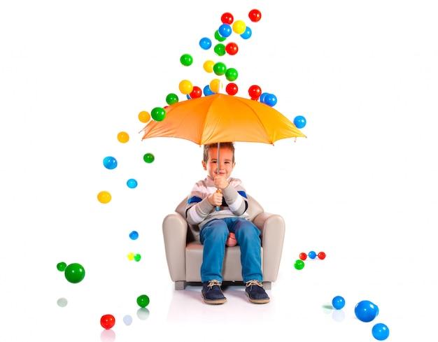 Garoto segurando um guarda-chuva em torno de bolas coloridas