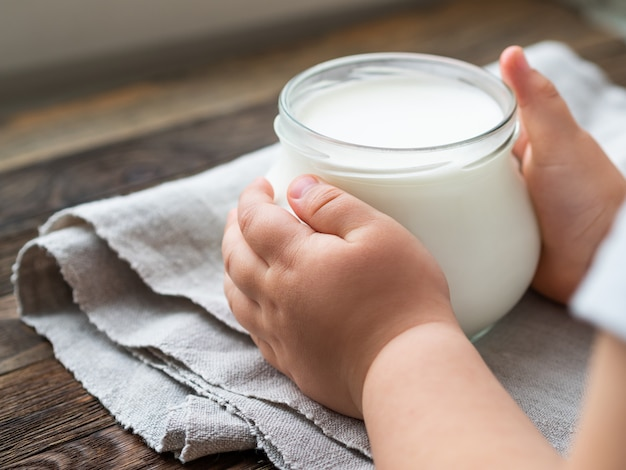 Garoto segurando um iogurte caseiro natural em uma jarra de vidro