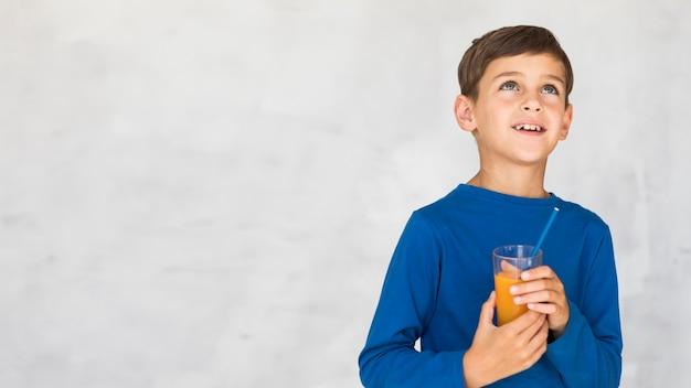 Garoto segurando um suco de laranja e olhando para cima
