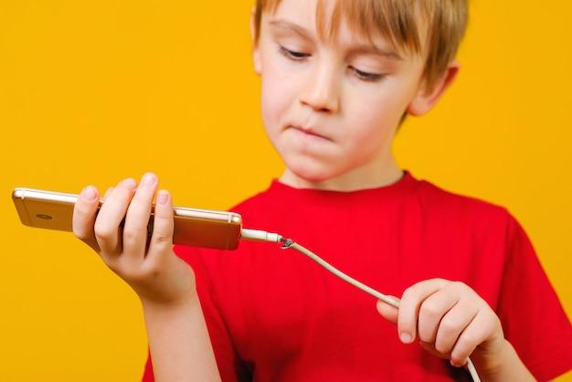 Garoto segurando um telefone móvel com um cabo de carregamento com defeito. o menino pensa como reparar cabel.