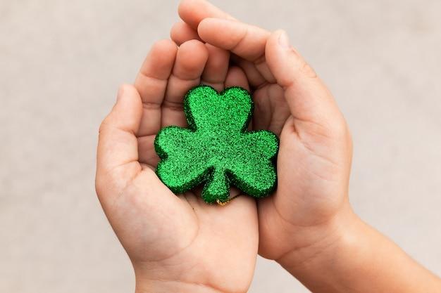 Garoto segurando um trevo brilhante verde nas mãos no dia de saint patricks