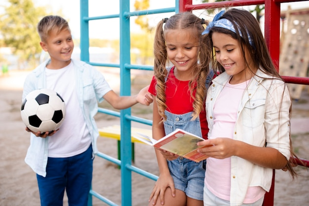 Garoto segurando uma bola enquanto as meninas leem um livro