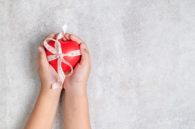 Garoto segurando uma forma de coração vermelho na mesa de mármore.