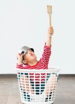 Garoto sentado no cesto de roupa suja