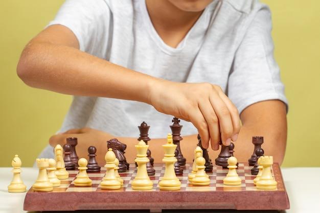 Garoto sentado perto do tabuleiro de xadrez e jogar jogo de xadrez