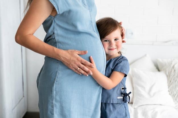 Garoto sorridente, abraçando sua mãe grávida