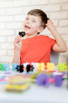 Garoto sorridente com flor de plástico