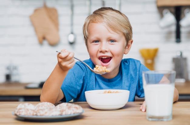 Garoto sorridente comendo cereal