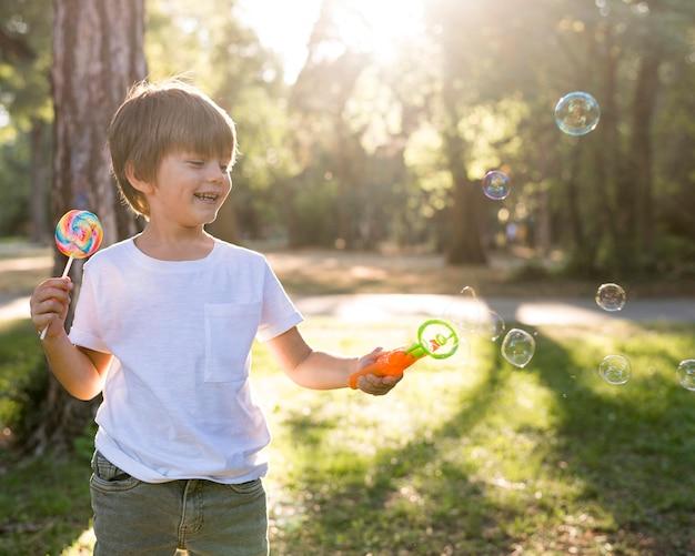 Garoto sorridente de tiro médio com balões de sabão