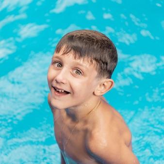 Garoto sorridente de tiro médio na piscina
