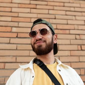 Garoto sorridente de tiro médio posando com óculos de sol