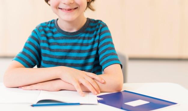 Garoto sorridente de visão frontal prestando atenção na aula