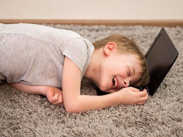 Garoto sorridente, deitado com a cabeça em um laptop