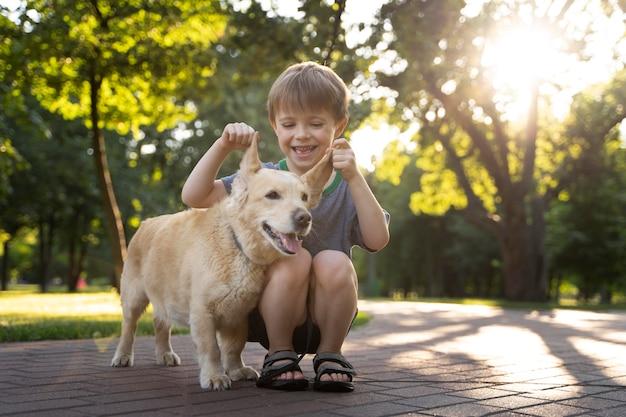 Garoto sorridente e cachorro no parque
