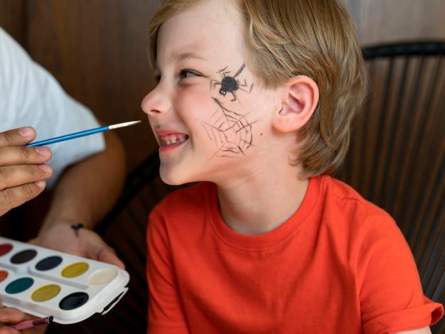 Garoto sorridente em close com o rosto pintado para o dia das bruxas
