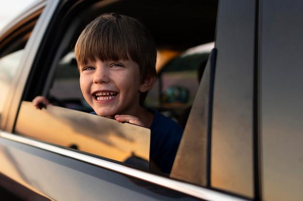 Garoto sorridente na janela do carro