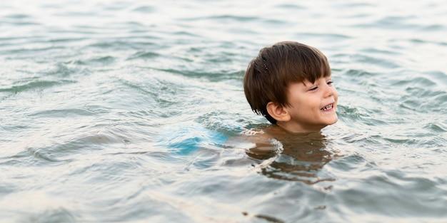 Garoto sorridente, nadar no mar