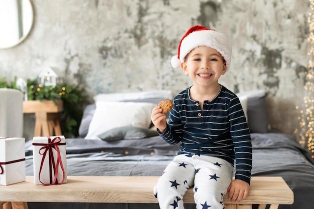 Garoto sorridente segurando um biscoito