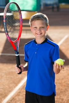 Garoto sorridente segurando uma raquete de tênis e uma bola