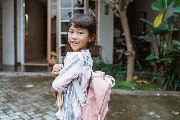 Garoto sorrindo para a câmera antes de ir para a escola