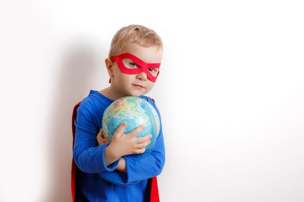 Garoto super-herói feliz segurando um globo na mão, o conceito de salvar o mundo