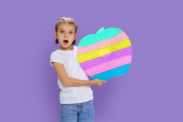 Garoto surpreso segurando enorme maçã anti-stress bolha habilidades motoras pop divertido criança segurando pop ...