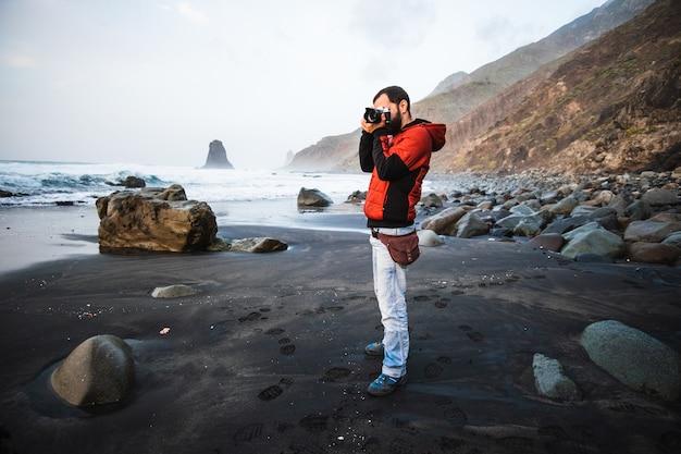 Garoto tirando fotos na praia