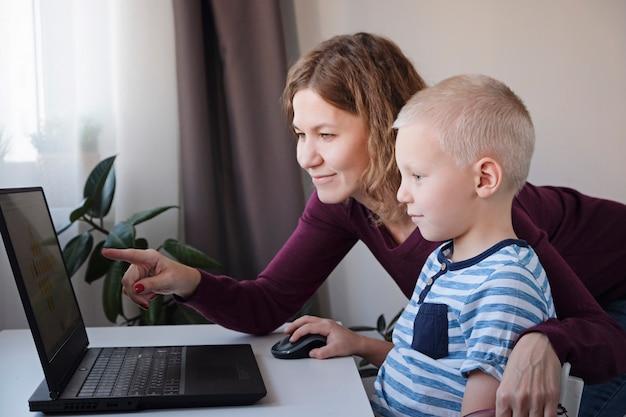 Garoto trabalhando em um computador junto com sua mãe em casa. e-aulas, educação para crianças.