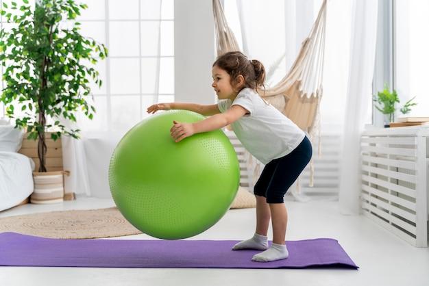 Garoto treinando com bola de ginástica e tiro completo
