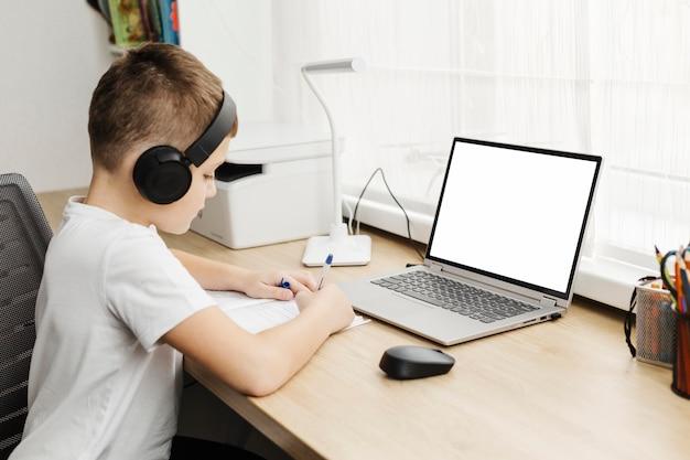 Garoto uma casa assistindo aulas online